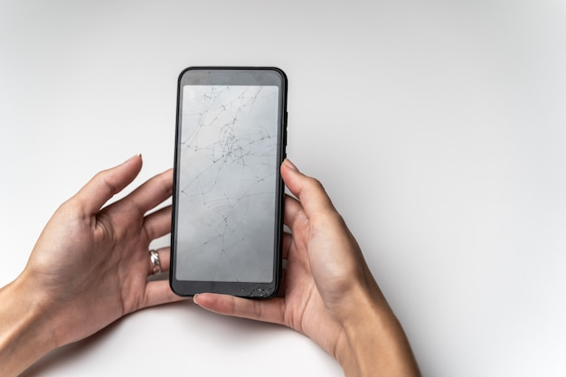 壊れた画面を持つ携帯電話を持つ女性の手。