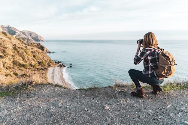 Молодая тазобедренная женщина с рюкзаком исследуя и фотографируя побережье на красивый день. концепция исследования и приключений