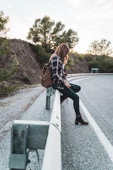 いくつかの車を待っている道路でヒッチハイクしている彼女のバックパックを持つ若いヒップ女性。探検と冒険の概念。