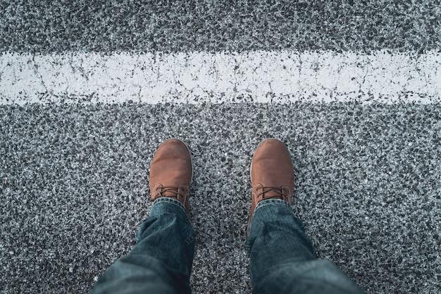 道路を横断する男性用のブーツと脚。探検と冒険の概念。