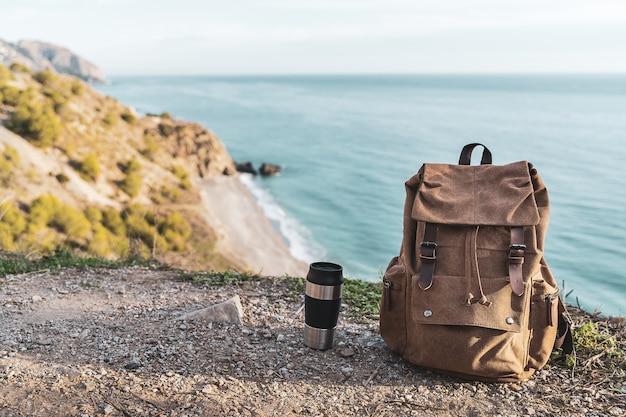 バックグラウンドで海岸とバックパックとコーヒーの魔法瓶。探検と冒険の概念
