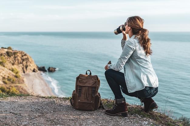 コーヒーを飲むと美しい日に海岸を探索するバックパックを持つ若いヒップな女性。探検と冒険の概念