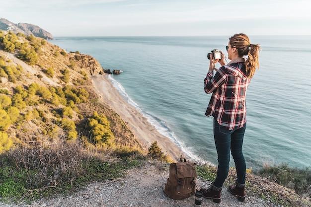 探索し、美しい日に海岸を撮影するバックパックを持つ若いヒップな女性。探検と冒険の概念