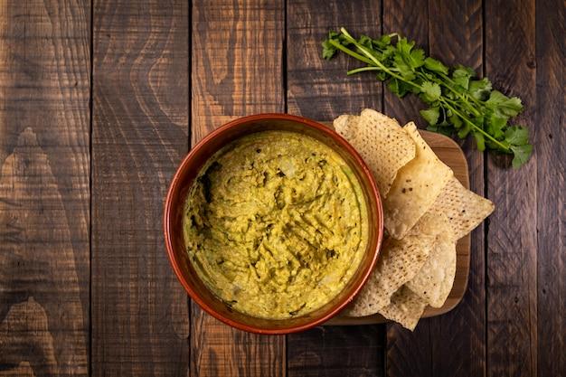 Домашнее свежее гуакамоле и чипсы готовы к употреблению. здоровая и вегетарианская еда.