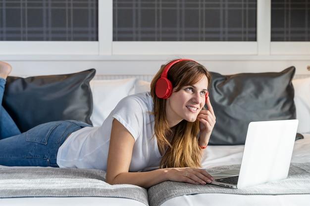 Молодая женщина, лежа в своей постели, работает на своем ноутбуке