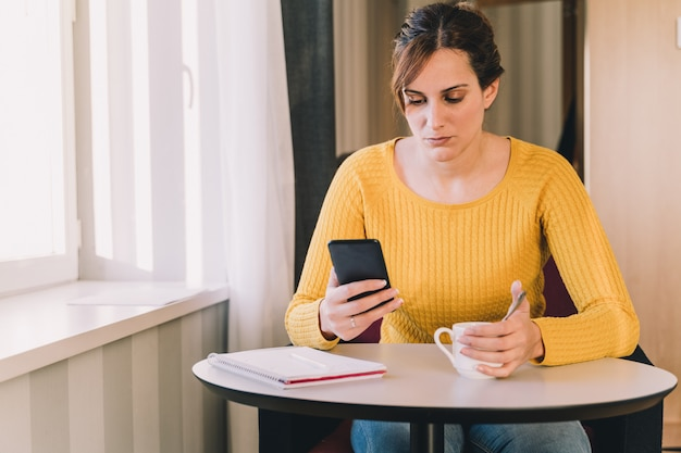 女性は一杯のコーヒーを飲みながら彼女の携帯電話をチェックします。仕事とソーシャルネットワークの概念。