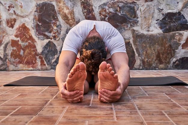 自宅でストレッチ筋肉の若い男。ホームトレーニングのコンセプトと健康的な生活。