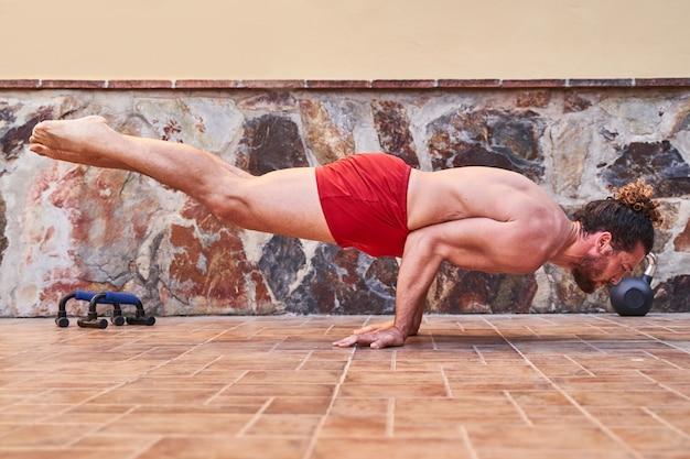 Мускулистый молодой человек делает стойку на руках у себя дома. концепция дома тренировки и здорового образа жизни.