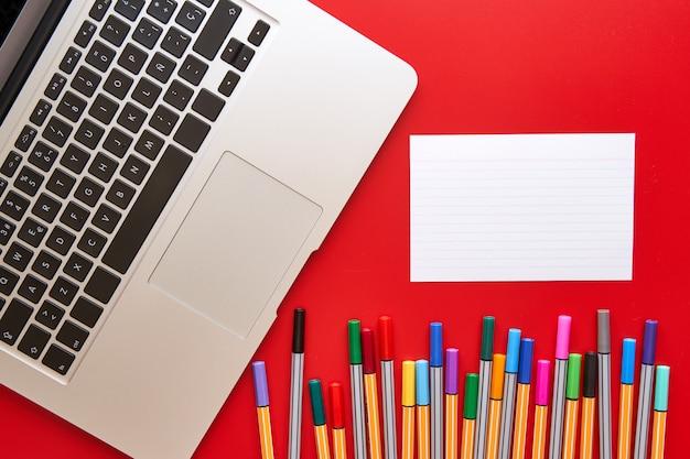 色付きのマーカー、ラップトップ、および赤の背景に書き込む用紙の空白のシート。デザインと創造性の概念。
