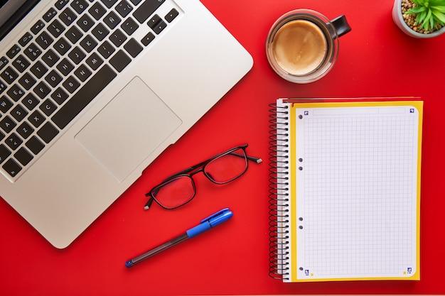 ノートブック、コーヒー、赤い背景の上のラップトップ。デザインと創造性の概念。