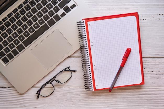 ノートと白い木製のテーブルの上のノートパソコン。デザイン、創造性、インスピレーションのコンセプト。