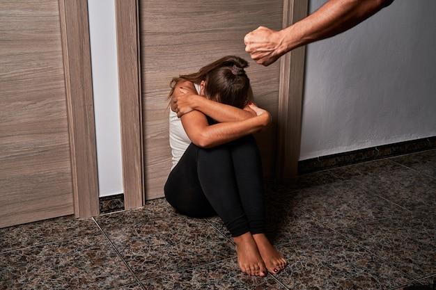 彼女のパートナーに虐待されている間床の上の若い女性