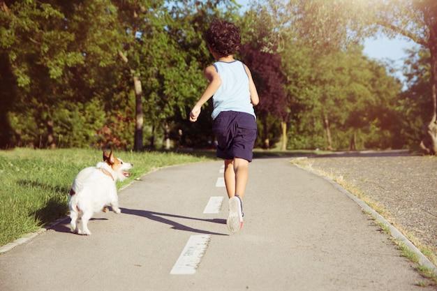 犬と子供が公園で走っています。リーシュオフ。友情の概念。