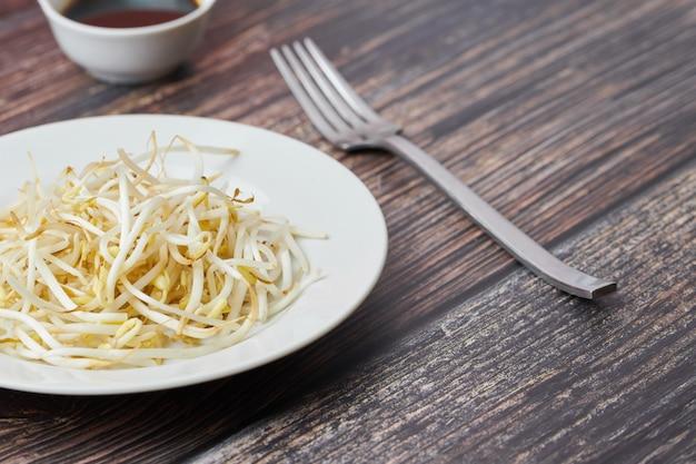 Бобы мунг прорастают в тарелку. сырье органическая здоровая пища. традиционное овощное блюдо в восточной азии.