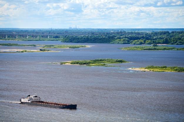 Баржа по реке плывет в порт для груза. транспорт для перевозки щебня и песка