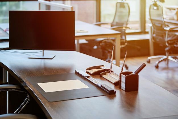 Современное офисное рабочее место. монитор на рабочем столе. бизнес рабочее место для начальника или начальника. утро солнечного света.