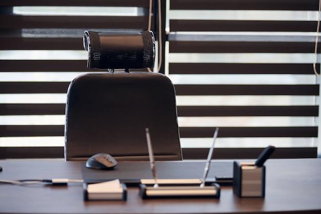 ビジネスオフィス職場。チーフ、ボスまたは他の従業員のための職場。テーブルと快適な椅子。ハーフオープンブラインドを通して光