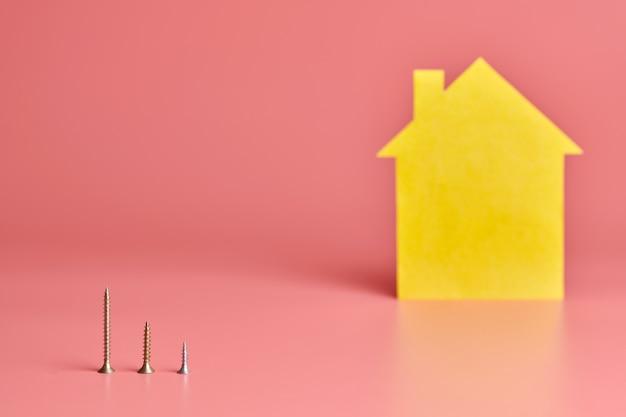 家の修理と改装されたコンセプト。家の改修。ネジと黄色の家形のピンクの背景の図。