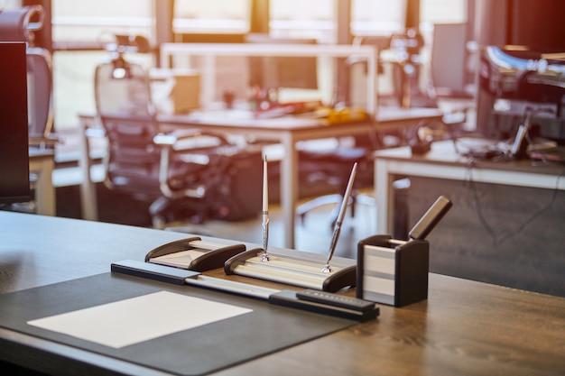 文房具と仕事場。上司、チーフ、スーパーバイザー、または近代的なオフィスで働く会社の長。快適なワークテーブルと革のコンピューターチェア。