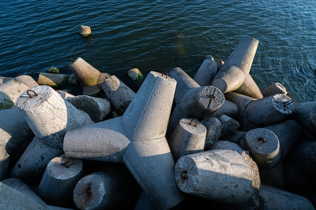 海水中の四脚防波堤。嵐の海の波、天候の影響、海岸の漂流から海岸構造物を保護するための、コンクリートのテトラポッドを備えた美しいサンセットシースケープ