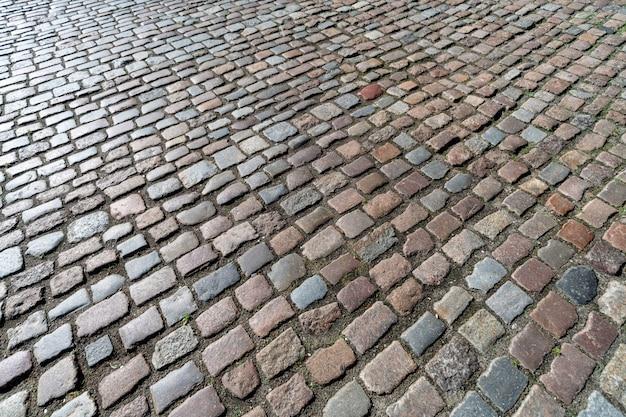 古い敷石パターン。市のダウンタウンの古代ドイツの玉石のテクスチャ。小さな花崗岩のタイル。アンティークグレーの舗装。