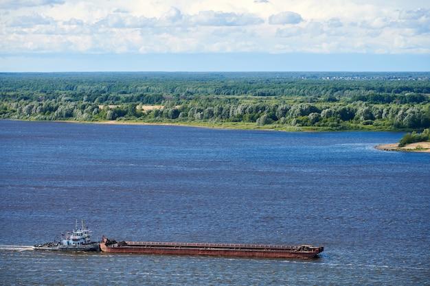 貨物を港に向けて航行する川のはしけ。砕石と砂の輸送のための輸送