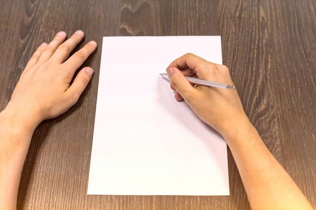 テーブルに座っているビジネスマンおよび右手にペンを保持しています。
