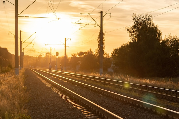 電車なしで夕暮れ時の鉄道。鉄道への美しい透視図。