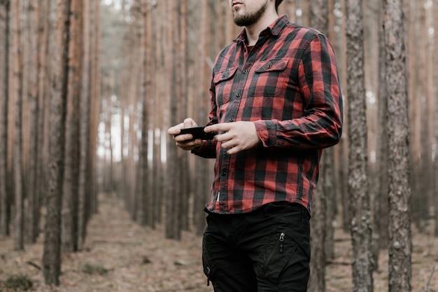 赤い格子縞のシャツと黒いミリタリーパンツの男は彼の手にスマートフォンを保持しています。