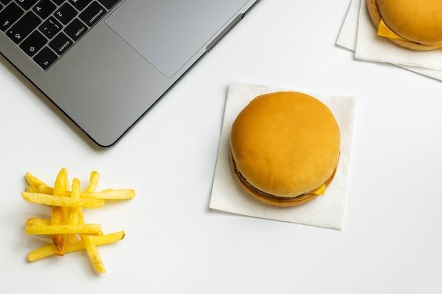 職場でのファーストフードのおやつ。職場でのラップトップ、ハンバーガー、フレンチフライ。