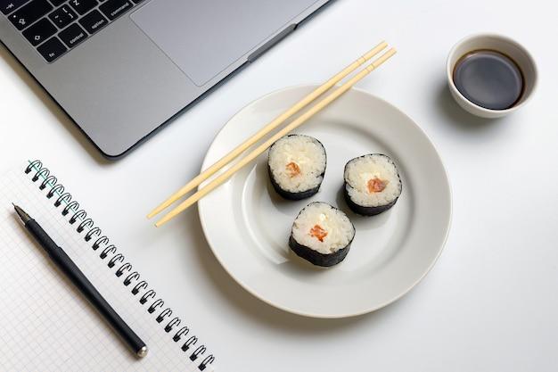 お寿司は仕事でおやつをロールします。寿司を食べるための休憩時間。