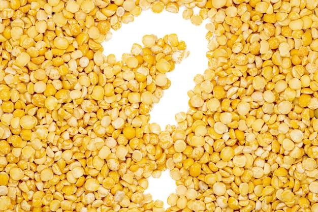 黄色分割乾燥エンドウ豆、疑問符、分離、クローズアップ、マクロ、トップビュー。