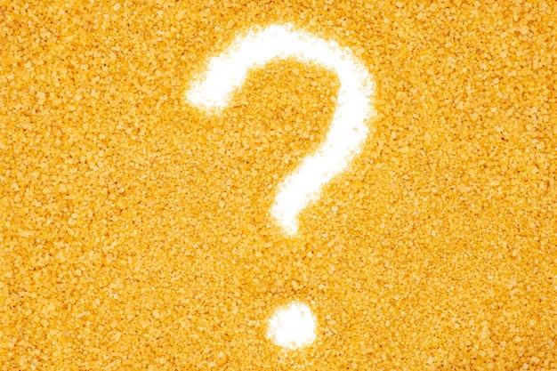 Желтый сахарный песок, вопросительный знак, конец вверх, макрос, взгляд сверху.