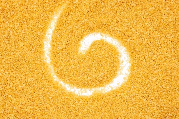 Желтый сахарный песок, спиральная форма, конец вверх, макрос, взгляд сверху.