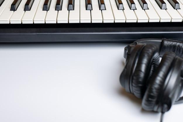 ピアノの鍵盤と分離されたコピースペース付きヘッドフォン。シンセサイザーキーボード