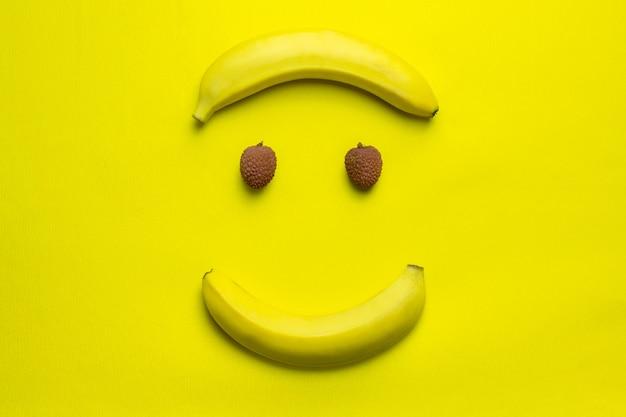 Личи и банан счастливой улыбкой на лице