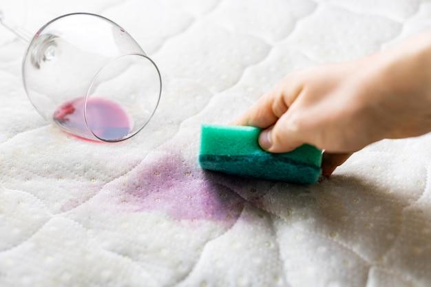 スポンジでワインの染みを掃除します。白いベッドシーツにこぼれたワイン