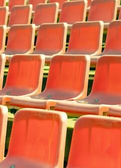 スタジアム席、赤い色。ファンなしのサッカー、フットボール、または野球スタジアムのトリビューン