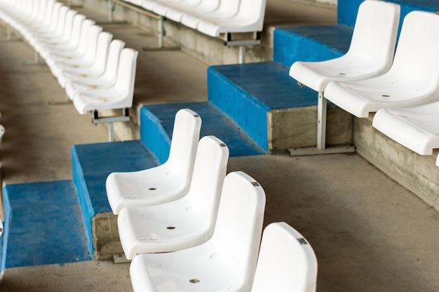 階段が付いている白い競技場の座席。ファンなしのサッカー、フットボール、または野球スタジアムのトリビューン