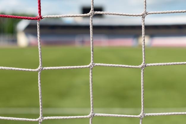 スタジアムでのサッカーのゴールサッカー場の背景。白と赤の網の色。