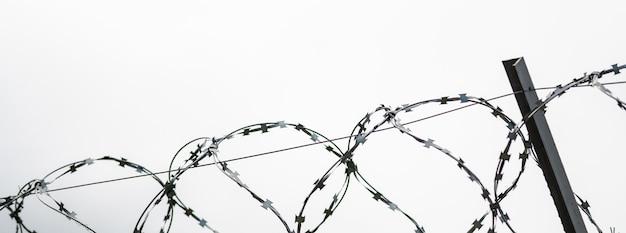 国境に有刺鉄線。禁止のためのフェンスの上の有刺鉄線