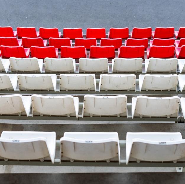 スタジアム席、赤と白の色。ファンなしのサッカー、フットボール、または野球スタジアムのトリビューン