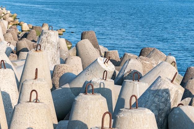 海の防波堤。コンクリートのテトラポッドと美しい夕日の海