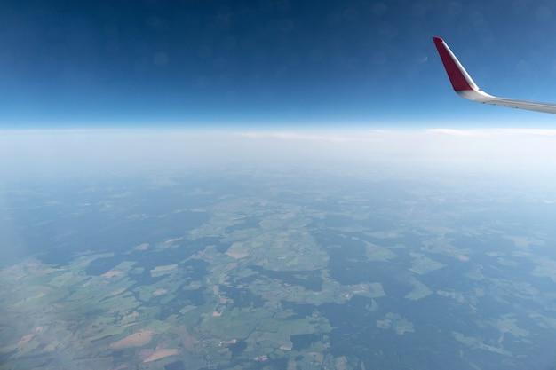 Вид из окна самолета на облачное небо и землю