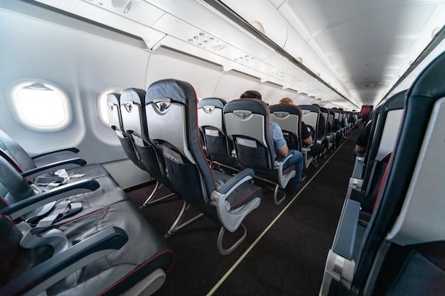 乗客と飛行機のキャビンの座席。新しい最も安価な低コスト航空会社のエコノミークラス。別の国への旅行旅行。飛行中の乱流。
