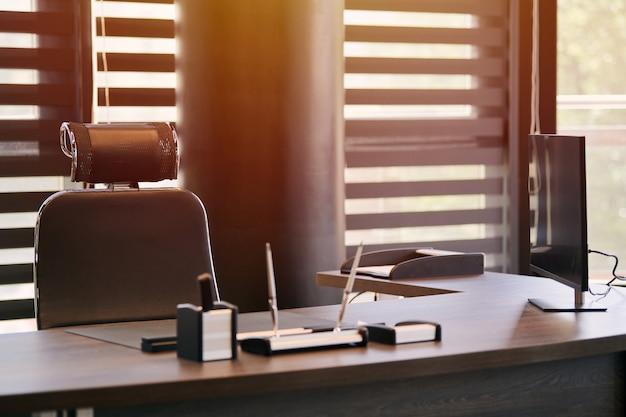 ビジネスオフィス職場。職場の主任、上司または他の従業員の日光。テーブルと快適な椅子。ハーフオープンブラインドを通して光