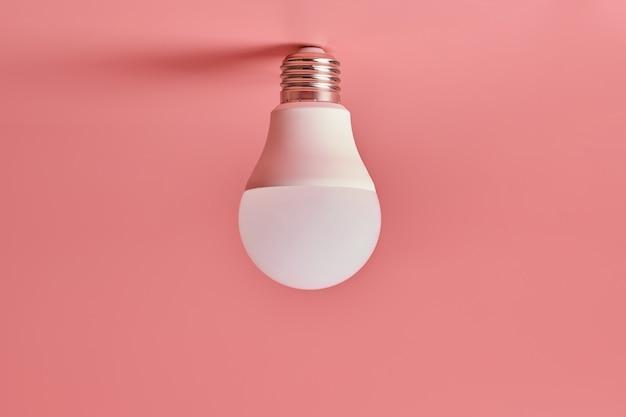 電球、コピースペース。省エネの最小限のアイデア。ピンク。