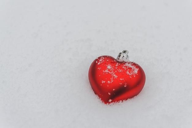 白い雪の背景に赤いハート