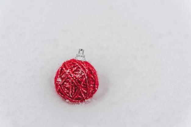 雪の自然の背景に赤い糸玉のクリスマスツリーの飾り