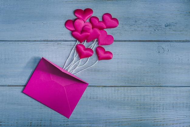 Розовые атласные сердечки над конвертом на деревянном фоне